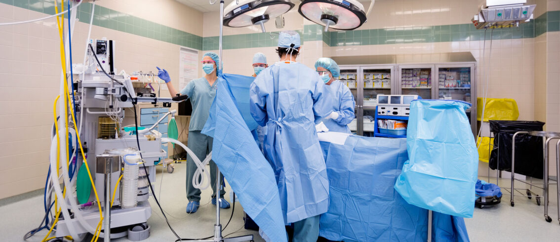 Surgical team operating on patient in theater in hospital